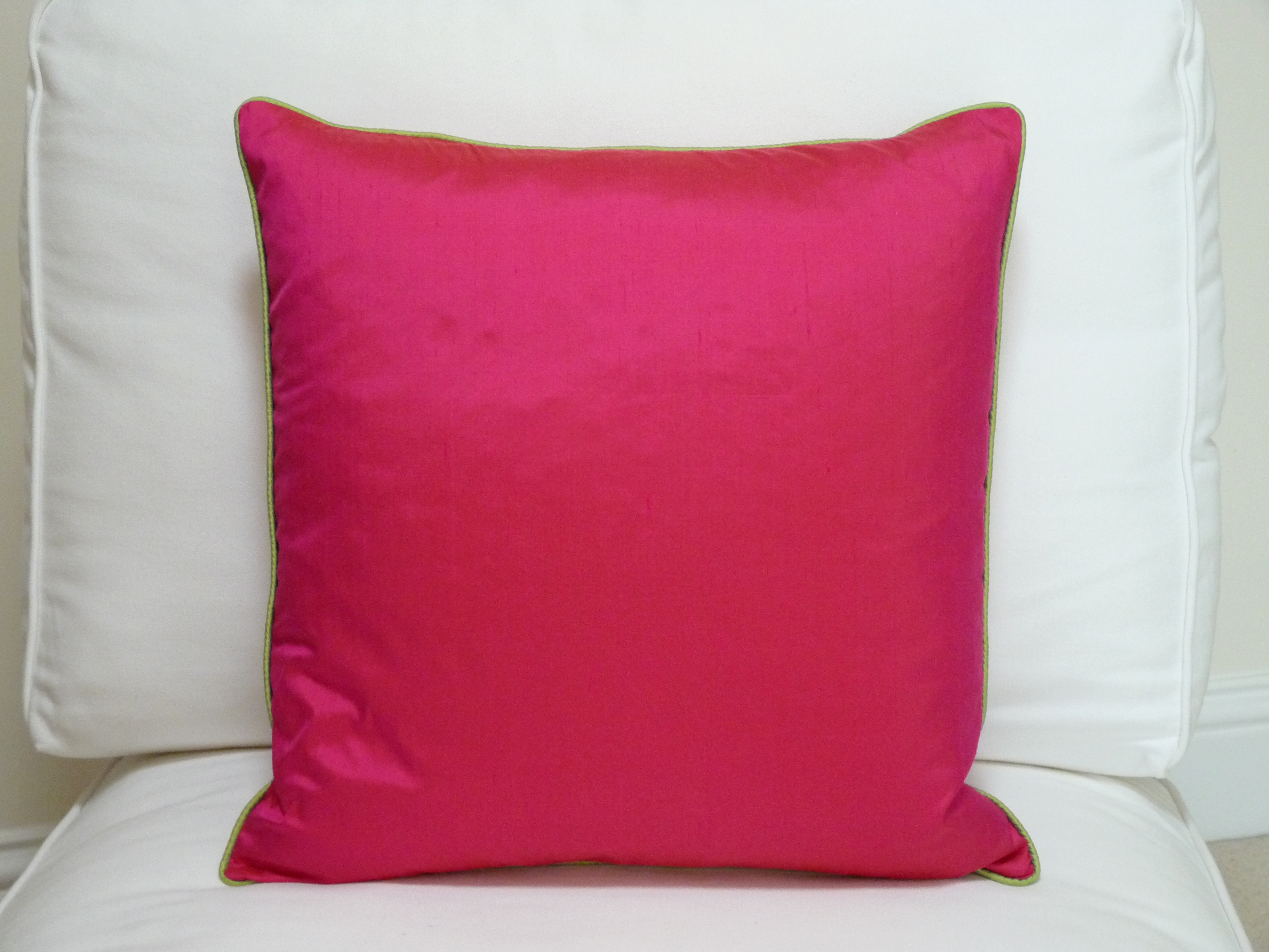 Contrast piped cushion. Cerise with lime piping.